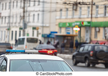 police car lights in city street with civilian cars traffic in blurry background in Tula, Russia