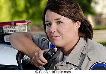 a female police officer holds the radio as she's about to talk into it.