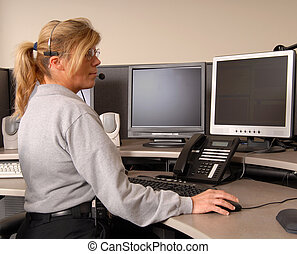 Police dispatcher working at console - A police dispatcher...