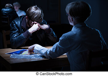 Police interrogation room - Young crying criminal in police...