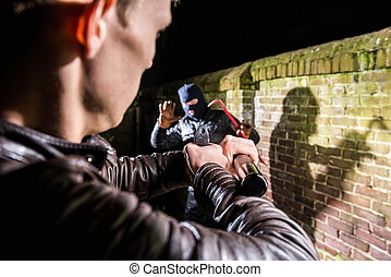 Police officer aiming torch and gun towards busted scared burglar by brick wall at night