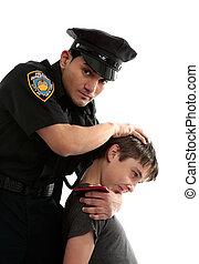 Police officer apprehending a teenage thief - A policeman...