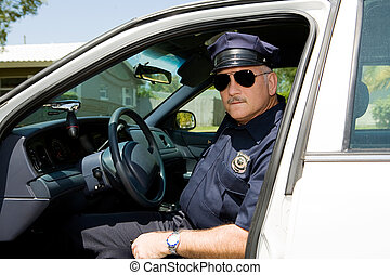 Handsome mature police officer on duty sitting in his squad car.
