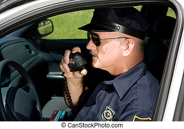 Police officer in squad car talking on his radio. Closeup view.