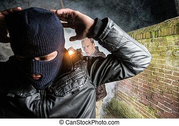 Police officer pointing gun towards busted masked burglar by brick wall at night