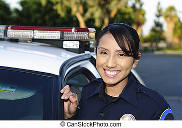police officer - a smiling Hispanic police officer next to...