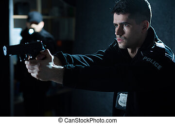 Police officer with handgun aiming at criminal