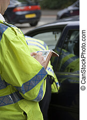 Police officer writing persons details whilst other officer searches car