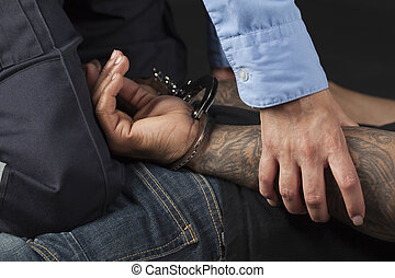 Police officer pinning down a handcuffed criminal