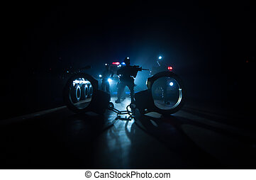 Police raid at night and you are under arrest concept. Silhouette of handcuffs with police car on backside. Image with the flashing red and blue police lights at foggy background.
