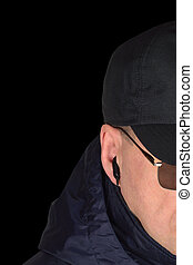 Police security guard staff policeman covertly listening on specop field situation, isolated black undercover agent covert operations surveillance earpiece closeup, caucasian european ethnicity, large detailed vertical studio shot, specops cop officer tactical eyeglasses, navy blue jacket, hood, cordura bodyguard baseball cap, riot control duty