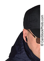 Police security guard staff policeman covertly listening on specop field situation, isolated undercover agent covert operations surveillance earpiece closeup, caucasian european ethnicity, large detailed vertical studio shot, black specops cop officer tactical eyeglasses, navy blue jacket, hood, cordura bodyguard baseball cap, riot control duty