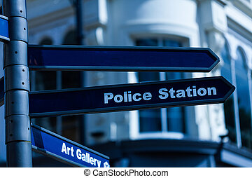 Police station street sign hanging on the lamppost. Arrow sign with police station direction.