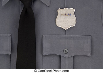 Wearing the badge, a closeup including the tie and top pocket of the police uniform.