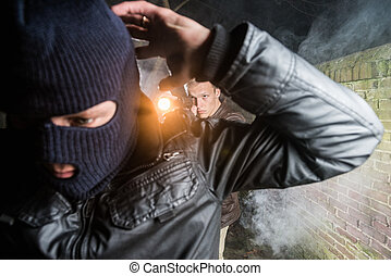 Policeman aiming pistol towards busted masked gangster at night