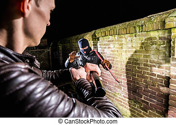 Policeman aiming torch and pistol towards busted scared cracksman by brick wall at night