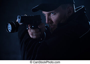 Policeman holding gun and flashlight