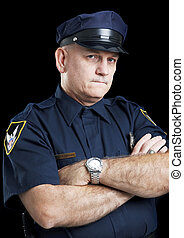 Portrait of a serious police officer with arms folded, against a black background.
