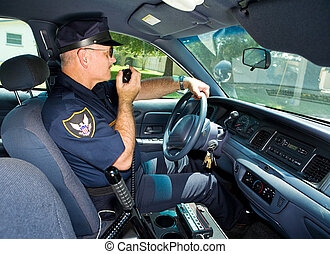 Policeman On Radio - Police officer in his squad car,...