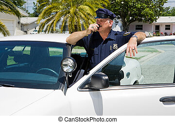 Policeman calls headquarters on his two way radio.