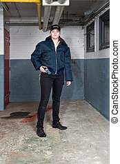 Policewoman looking tough and posing in a basement crime...