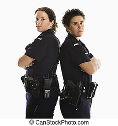Policewomen back to back. - Portrait of two mid adult...