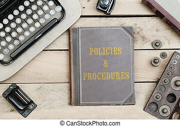 Policies and Procedures on old book cover at office desk with vintage items
