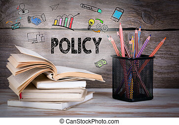 Policy. Stack of books and pencils on the wooden table.