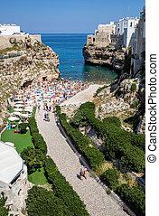 People relax and swimming on lovely beach Lama Monachile in Polignano a Mare, Adriatic Sea, Apulia, Bari province, Italy,