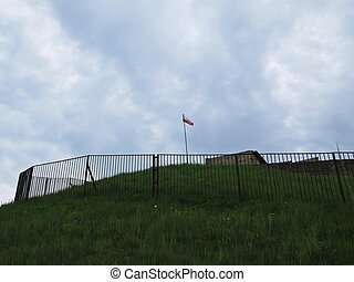 Polish Flag in Wind on a Tower of Stronghold with Clouds in Background