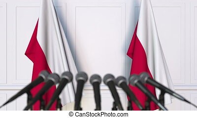 Polish official press conference. Flags of Poland and...