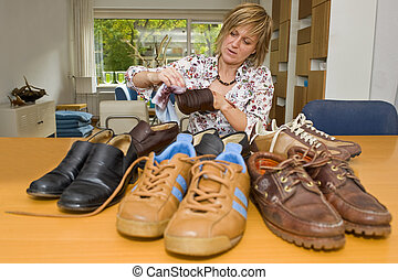 Polishing shoes - A woman at a table in a living room ...
