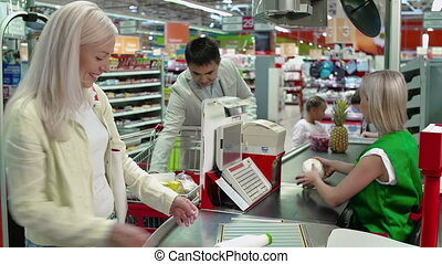 Polite Cashier - Close up of family at cash box putting...