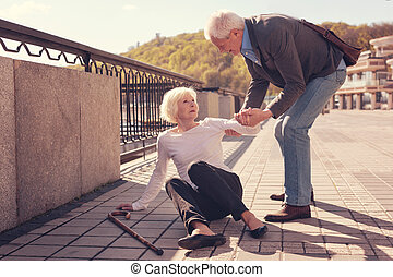 Polite elderly man helping a woman to get up
