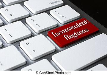 Political concept: Inconvenient Regimes on white keyboard