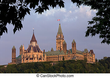 The canadian Parliament in the late day sun framed with green leaves during summer.