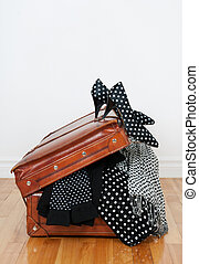Polka dot clothing in a vintage leather suitcase