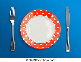 polka dot red plate with fork and knife top view on blue background
