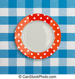 Polka dot red white dinner plate on blue checked tablecloth...