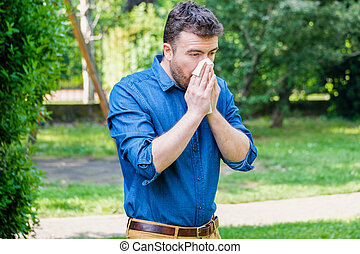 Pollen allergy in springtime concept. Man sneezing in a tissue