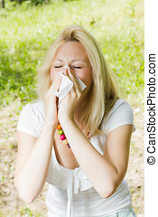 pollen allergy - Young woman blowing nose outdoor, pollen...