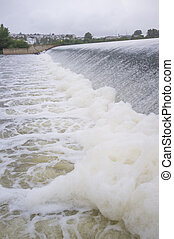 Polluted river full of foam at diversion dam. Town skyline at bottom