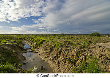 Polluted stream with landscape and blue skies