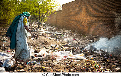 Pollution and poverty : Indian old female sitting for warmup herself near fire in garbage,