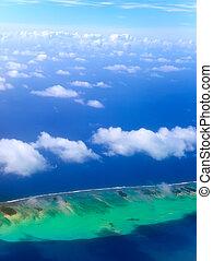 Polynesia. The atoll in ocean through clouds. Aerial view....