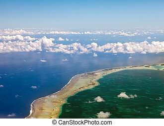 Polynesia. The atoll in ocean through clouds. Aerial view.