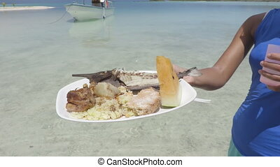 Polynesian fish barbecue traditional French Polynesia food on the beach - motu picnic cruise tour in Fakarava, Tahiti, French Polynesia. Grilled fish, coconut bread, tahitian rice, pork, watermelon