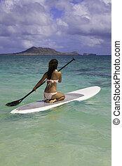 polynesian girl on a standup paddle board