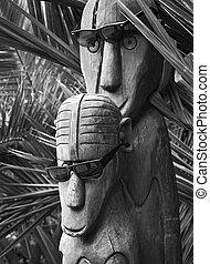 Polynesian wooden idols in sunglass. Palm trees