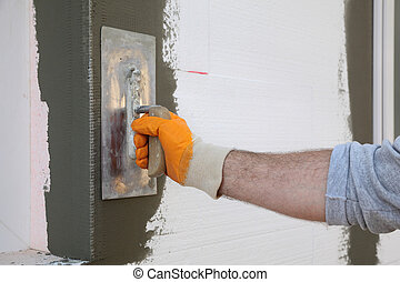 Polystyrene wall insulation - Worker spreading mortar over ...